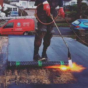 Curt Marshall heats the roofing felt with his gas torch to ensure a watertight seal.